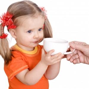девочке дают чашку